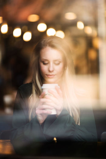 Coffee Shop Beautiful Woman Blond Hair Casual Clothing Coffee - Drink Coffee Cup Communication Drink Drinking Front View Holding Illuminated Indoors  Leisure Activity Lifestyles Long Hair Mobile Phone One Person Real People Sitting Through The Window Women Young Adult Young Women