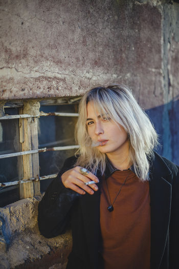 Portrait of woman smoking cigarette while standing against wall
