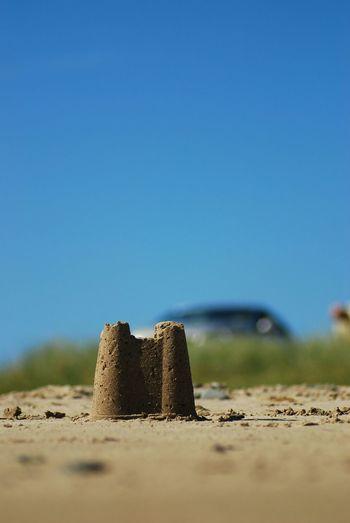 Sandcastle on beach against clear blue sky