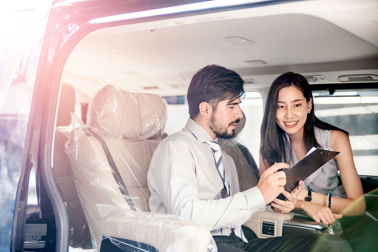 Young couple holding smart phone while sitting in car