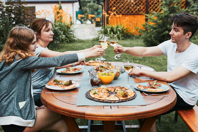 Friends making toast during summer picnic outdoor dinner in a home garden