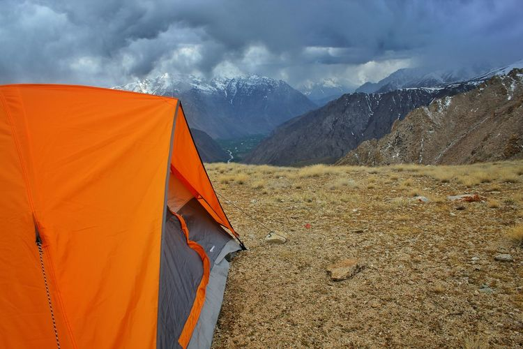 Tent in mountains against cloudy sky