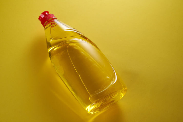 Close-up of yellow glass bottle on table