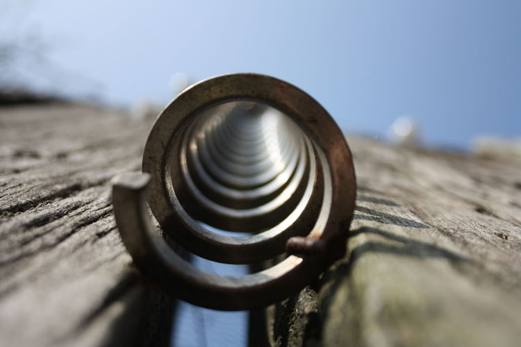 Close-up of rusty metal on wood against sky
