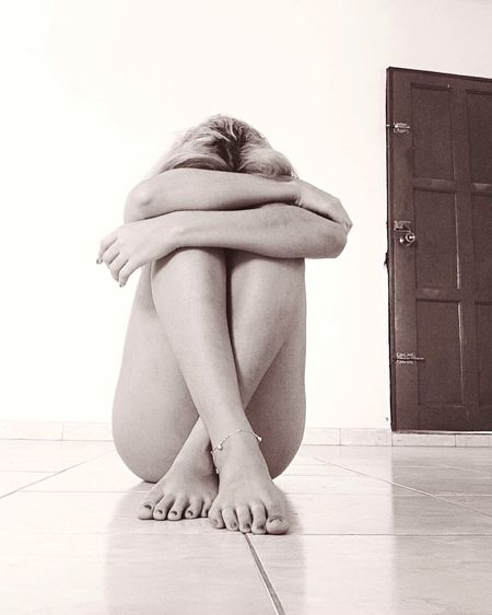 Depressed Naked Woman Sitting On Floor At Home
