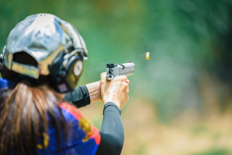 The woman's hands are practicing firing guns and shelling out. Activity Adult Aggression  Aiming Clothing Day Focus On Foreground Gun Headshot Headwear Helmet Holding One Person Outdoors Real People Rear View Shooting A Weapon Sport Target Shooting Weapon Women