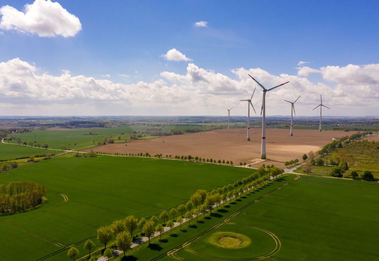 aerial view of agricultural fields with an avenue - wind turbines in the background Environment Wind Turbine Sky Landscape Cloud - Sky Field Renewable Energy Nature Turbine Environmental Conservation Fuel And Power Generation Scenics - Nature Beauty In Nature Wind Power Green Color No People Plant Tranquility Outdoors Alternative Energy Land Day