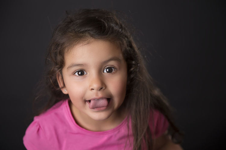 Close-up portrait of girl against black background