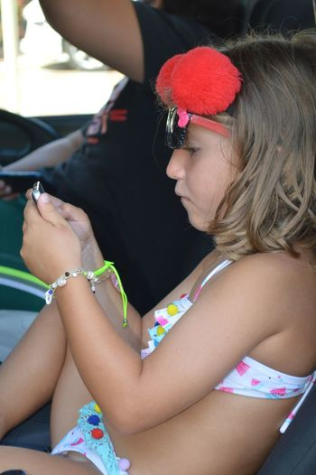 Side View Of Girl Wearing Swimwear While Using Phone In Car
