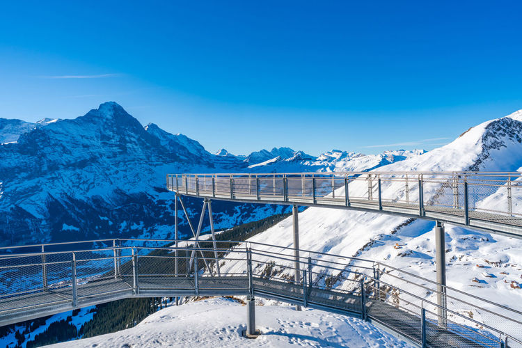 Bridge over snowcapped mountains against blue sky