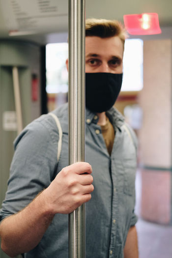 Portrait of man wearing mask holding metallic pole in train