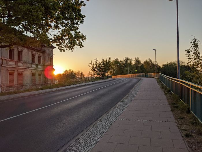 Empty road along buildings at sunset