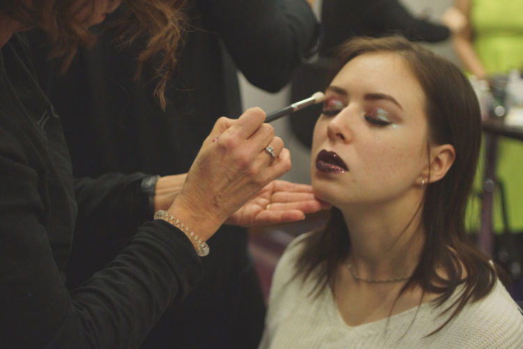 Beautician applying make-up to woman