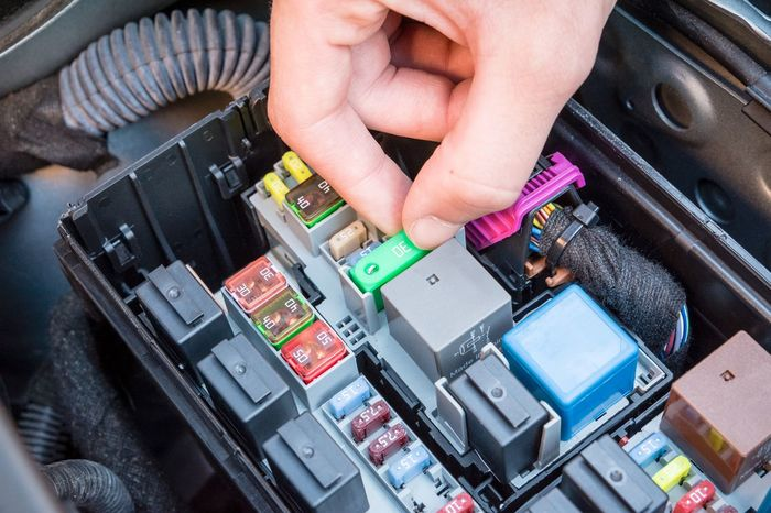 Hand checking a fuse in the fuse box of a modern car engine Car Checking Close-up Day Electric Parts Electricity  Engine Fuse Box Human Hand One Person People Real People Technology
