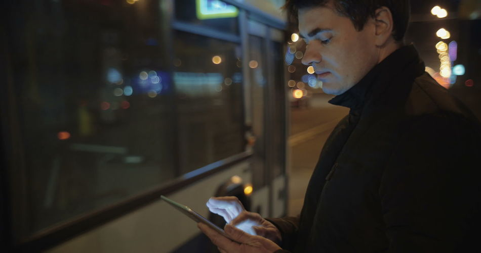 Midsection of man using mobile phone at night