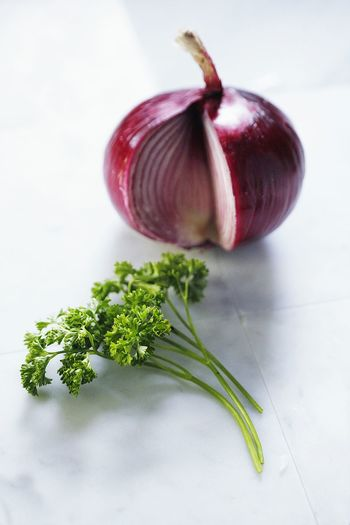 Close-up of onion and coriander leaves on table