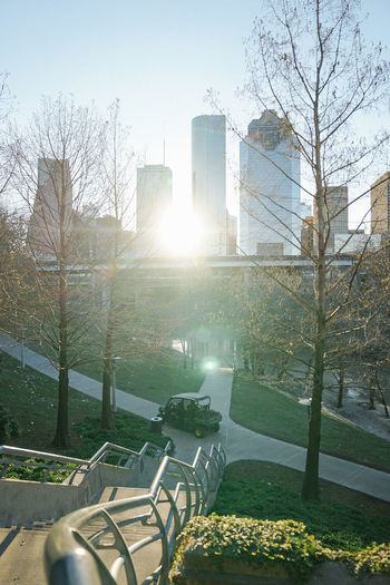 Empty park bench by buildings in city against sky