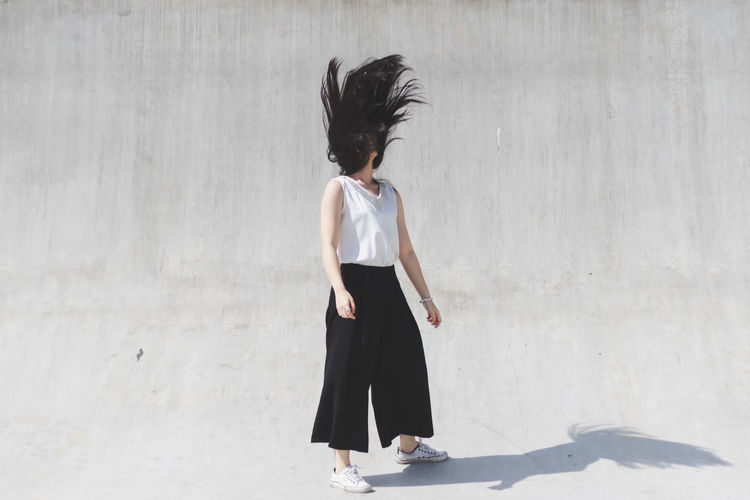 Young woman shaking head while standing on street