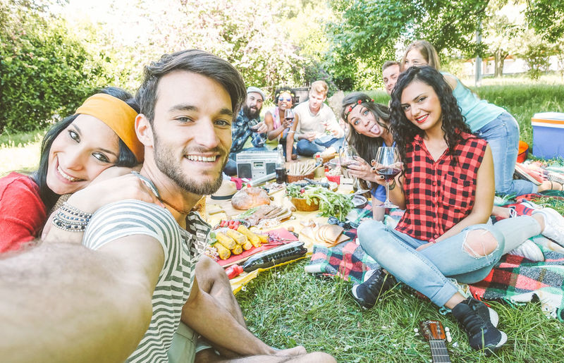 Friends taking selfie at picnic party People Picnic Garden Happy Friends Smiling Laughing Group Of People Young Adult Youth Happiness Young Men Togetherness Young Women Emotion Men Friendship Bonding Portrait Enjoyment Casual Clothing Leisure Activity Looking At Camera Sitting Selfie