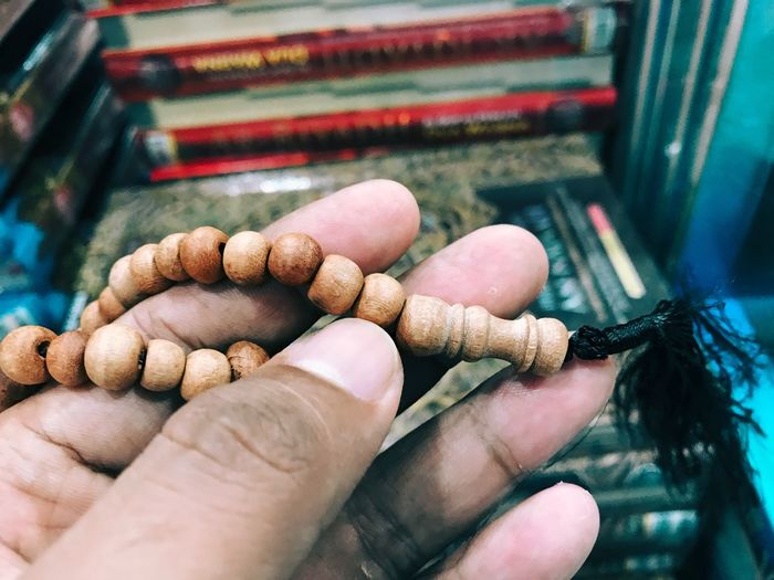 Close-up of hand holding prayer beads
