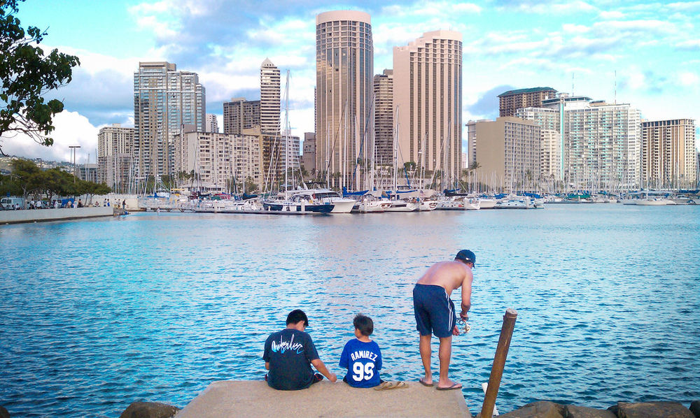 Father and sons fish on a slab overlooking the waters of Ala Moana Beach Park in Honolulu, Hawaii with the building and hotel skyline of famous, tourist favorite Waikiki in the background Ala Moana Ala Moana Beach Park Family Global Warming Hawaii Oahu Siblings Waikiki Boys City Cityscape Family Values Father Fathers Day Fish Fishing Friendship People Sea Sky Skyscraper Togetherness Urban Skyline Vacations Water