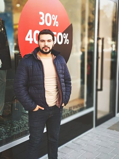 Portrait of confident man standing with hands in pockets against store