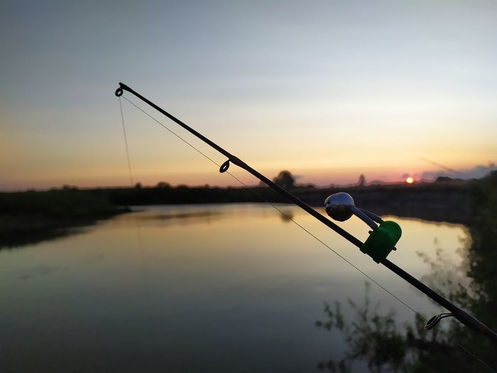 Silhouette fishing rod on lake against sky at sunset
