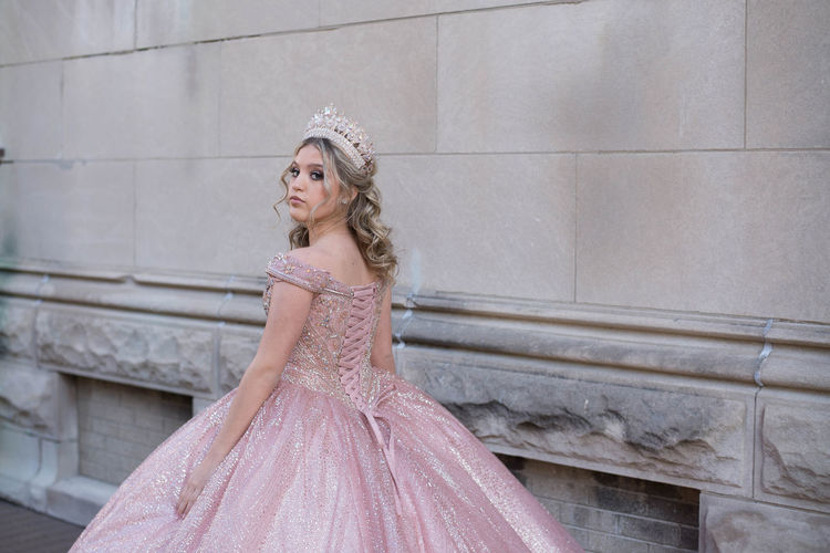 Portrait of beautiful bride wearing crown while standing against wall