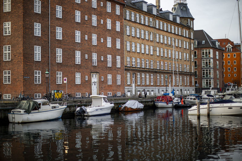 Sailboats moored on canal by buildings in city