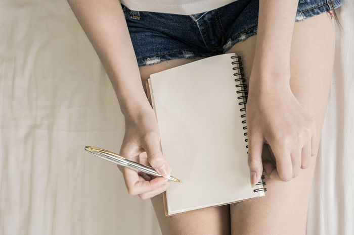 Adult Book Close-up Communication Day Diary Holding Human Body Part Human Hand Indoors  Low Section Midsection Note Pad One Person One Woman Only One Young Woman Only Pen Portable Information Device Real People Sketch Pad Wireless Technology Women Working Young Adult Young Women