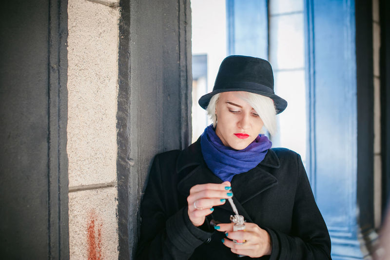 Close-up of young woman preparing electronic cigarette by column