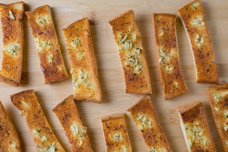 Garlic bread stick arranges on the wooden board Cooling  Arrangement Baked Baked Pastry Item Bread Sticks  Brown Color Cooked Food Garlic Bread Monotone Ready-to-eat Wooden Board