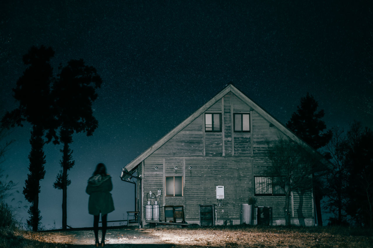 Rear view of woman standing on footpath by illuminated house against sky at night