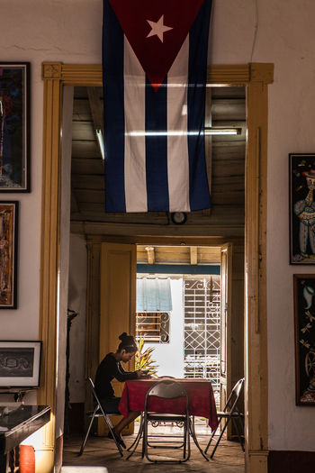 A woman sits in front of the backyard door of a colonial house, under the Cuban flag. Cuba Cuban Cuban Flag Cuban Lady Cuban Life Daily Life Flag Lifestyles Real People Reflection Relaxing Trinidad Trinidad, Cuba