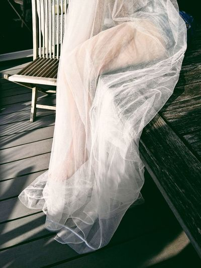 Low Section Of Woman Sitting On Wooden Bench With White Tulle Netting