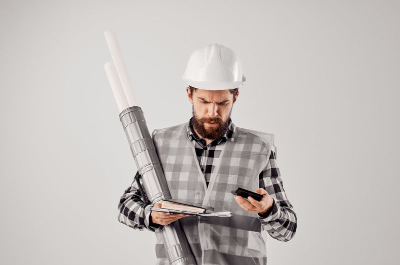 Man using smart phone against white background