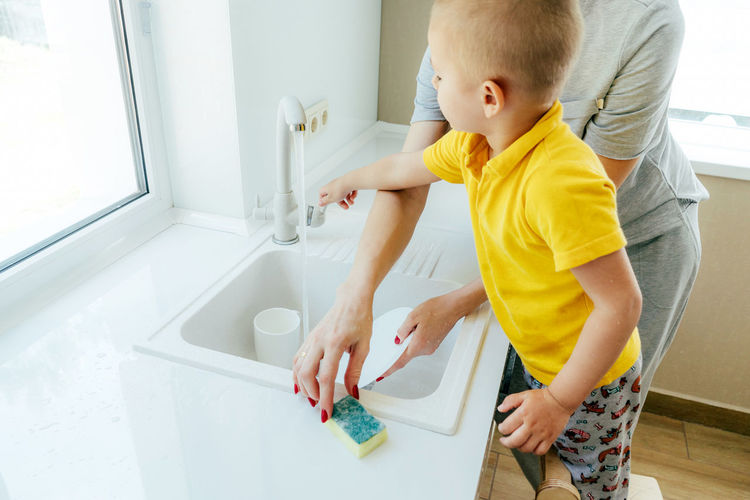 Rear view of siblings playing in bathroom at home