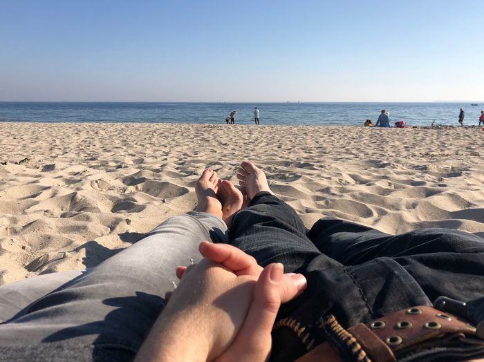 Low section of couple holding hands while lying at beach