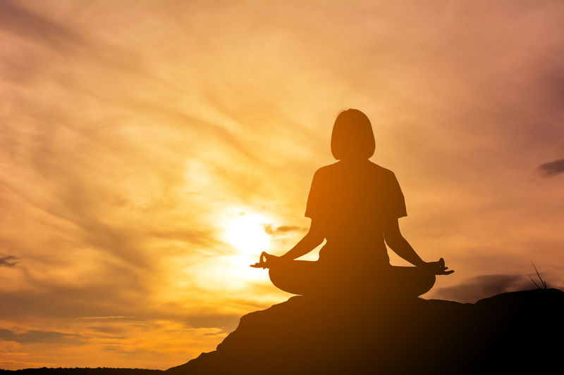 Woman Meditating Against Sunset Sky