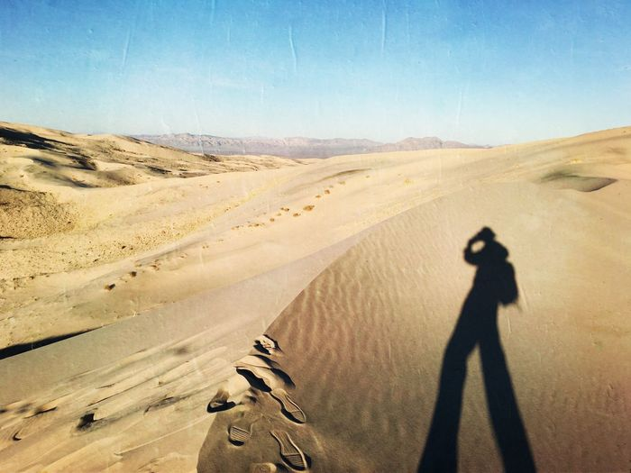 Shadow of man on sand dune in desert against clear sky