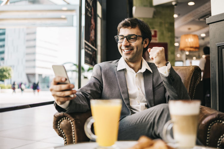 Smiling businessman using mobile phone at restaurant
