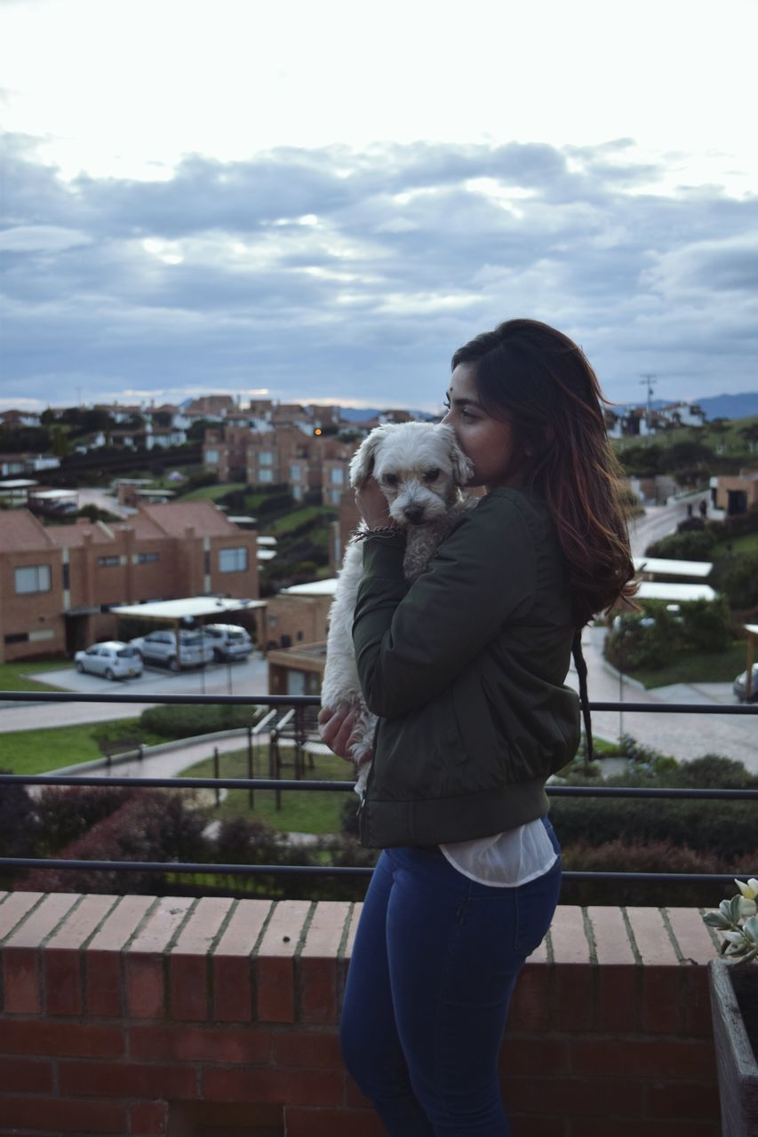 Side View Of Woman Holding Dog On Terrace Against City