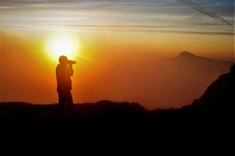 Silhouette man standing on mountain against orange sunset sky