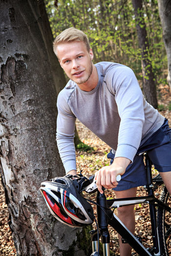Portrait Of Man Sitting On Bicycle In Forest