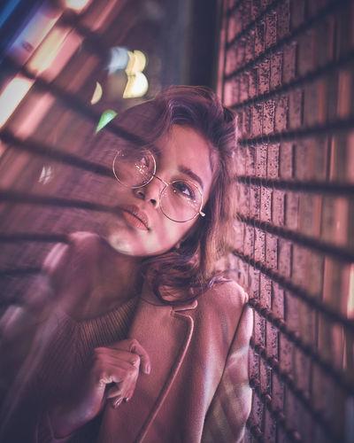 Young woman in nightclub seen through glass