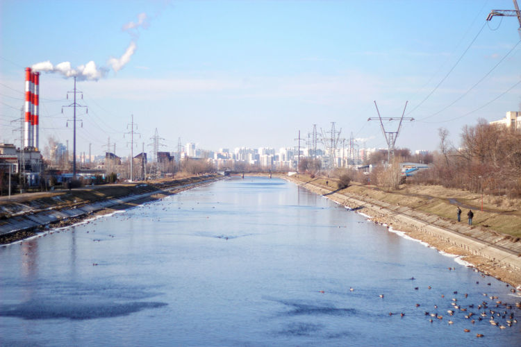 Scenic view of frozen river against sky in city