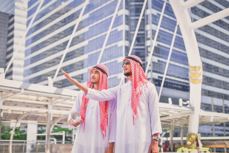 Businessmen in traditional clothing standing against modern buildings