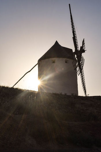 Low angle view of traditional windmill on field against sky during sunset