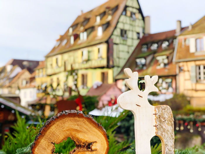 Close-up of cross against buildings in city