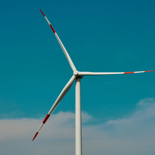 Wind turbine in front of a blue sky with white clouds